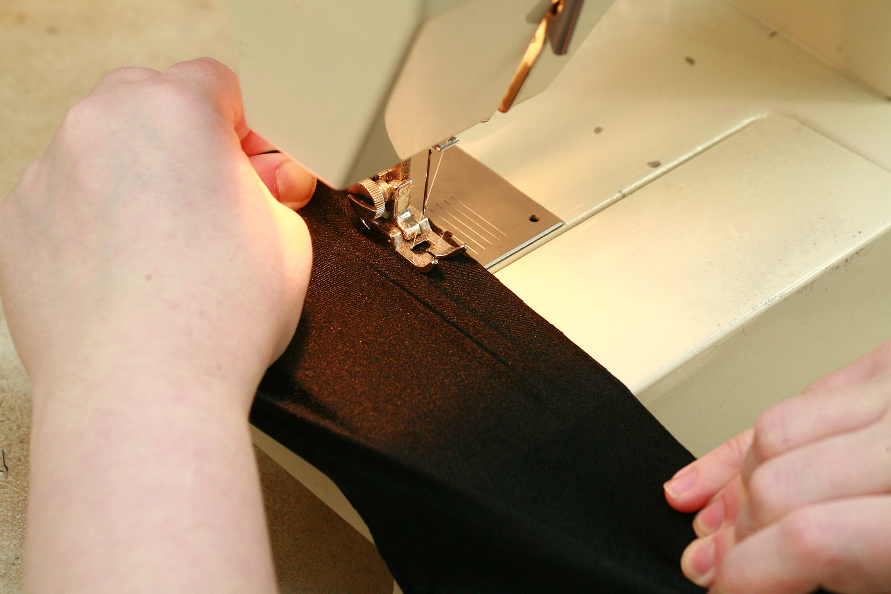Two hands are sewing spandex with a regular sewing machine.