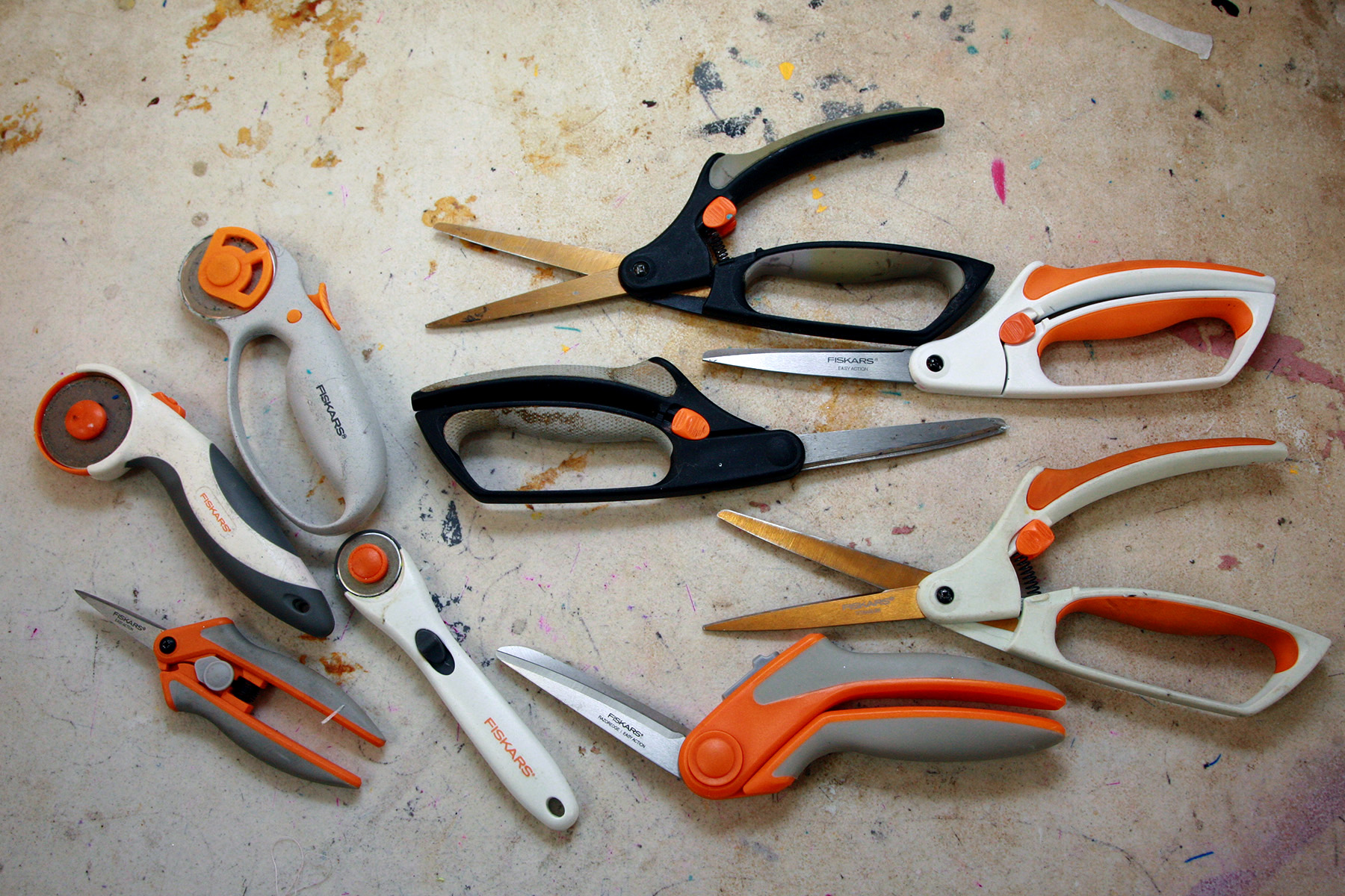 A section of Fiskar scissors - all orange, white, and black - are shown on a work table.