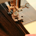 Two hands guide a piece of black spandex fabric through a sewing machine.