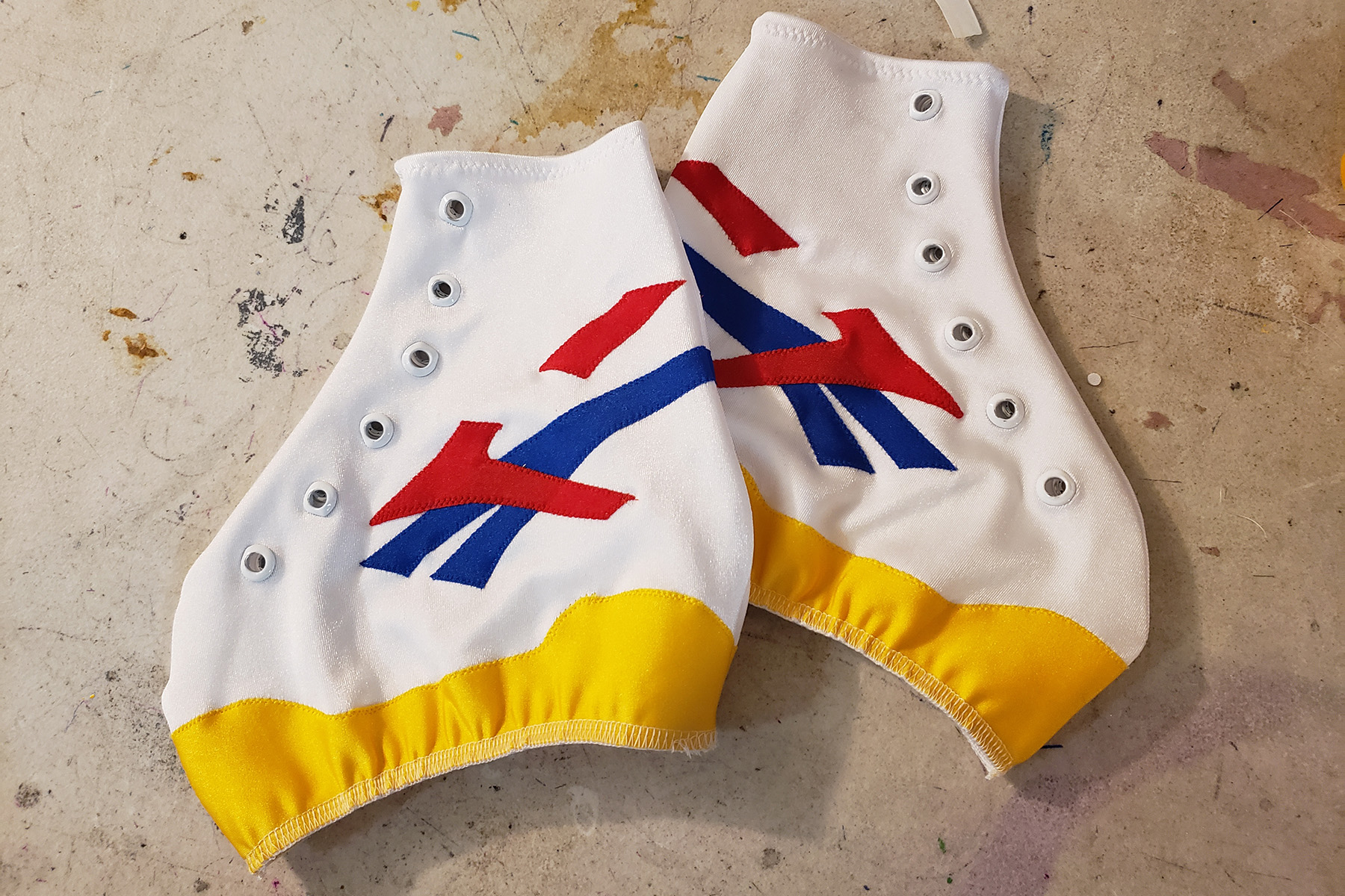 A pair of custom skate covers, made to look like sneakers. They are white, with accents of yellow, red, and blue.