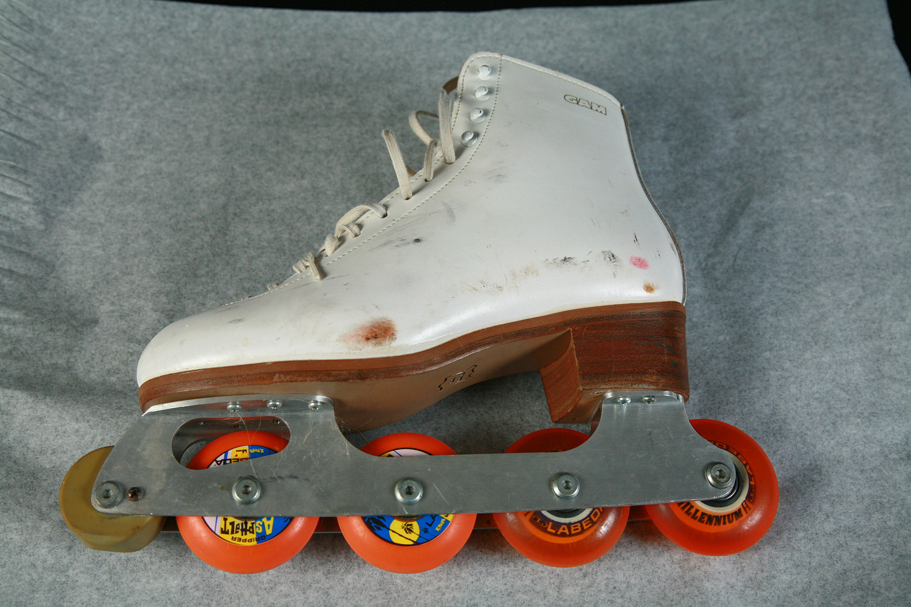 A white inline roller figure skate is pictured against a sheet of translucent white paper.