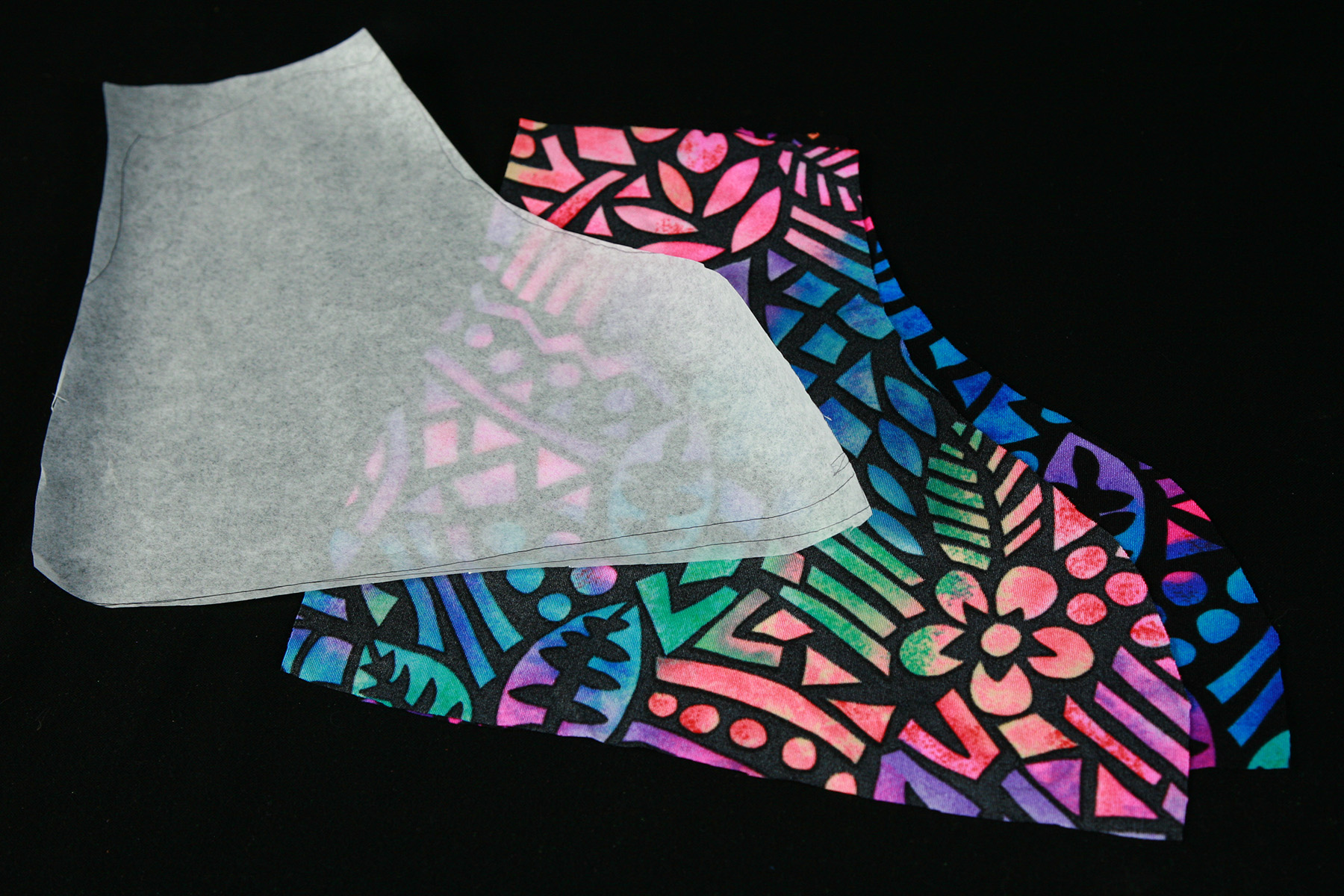 A skate cover pattern cut from translucent white paper rests against a piece of brightly coloured fabric that has been cut to shape with the pattern pictured.