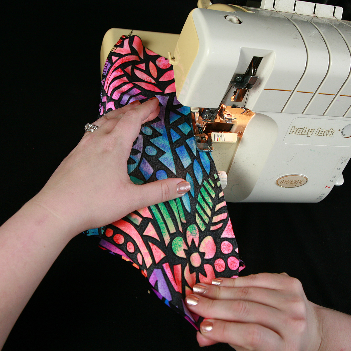 A pair of hands uses a serger to sew a skate cover out of brightly printed fabric.