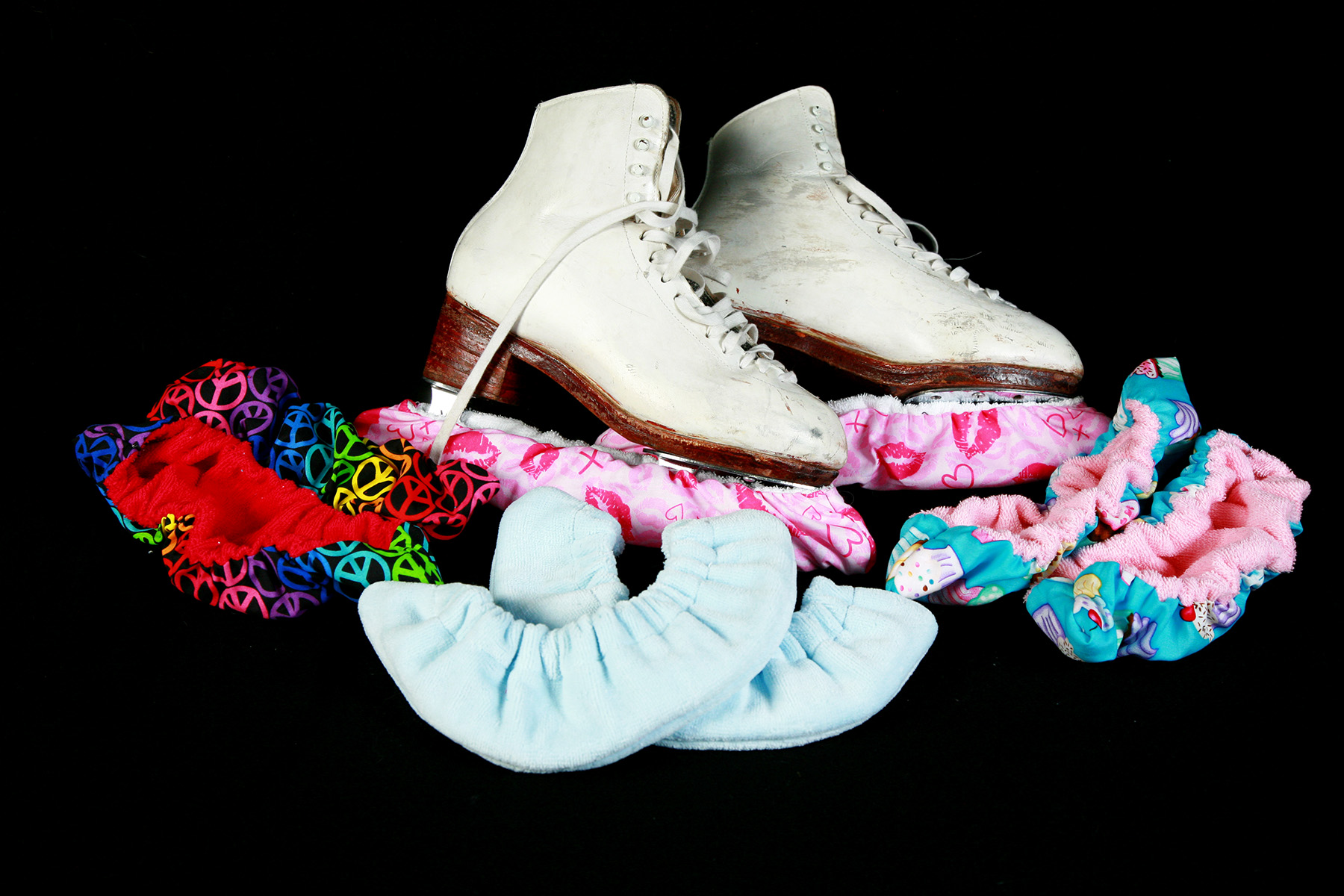 A pair of skates is surrounded by colourful fabric blade covers.
