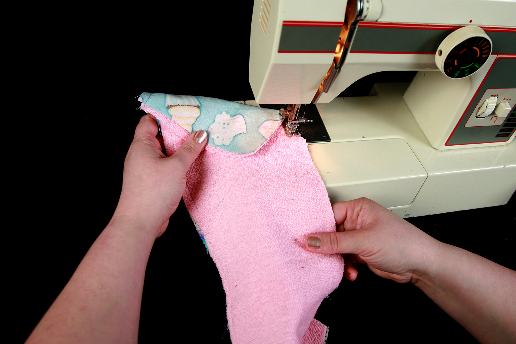 A pair of hands uses a sewing machine to sew a strip of pink terrycloth