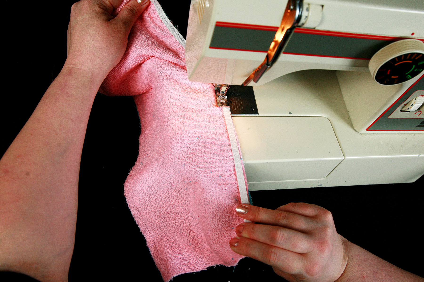 A pair of hands uses a sewing machine to sew a strip of elastic to a piece of pink terrycloth.