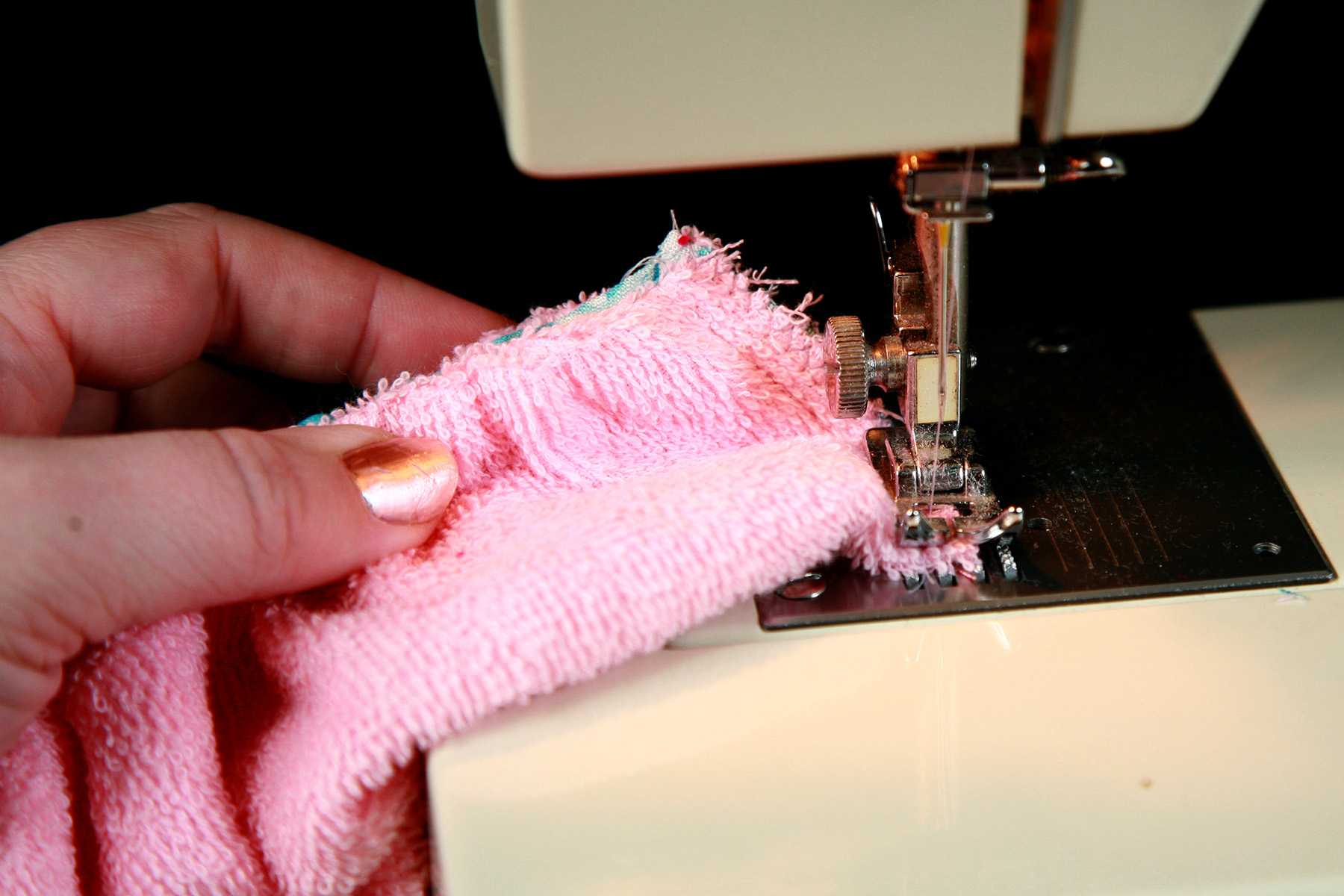 A pair of hands is using a sewing machine to sew side seams on a soaker.