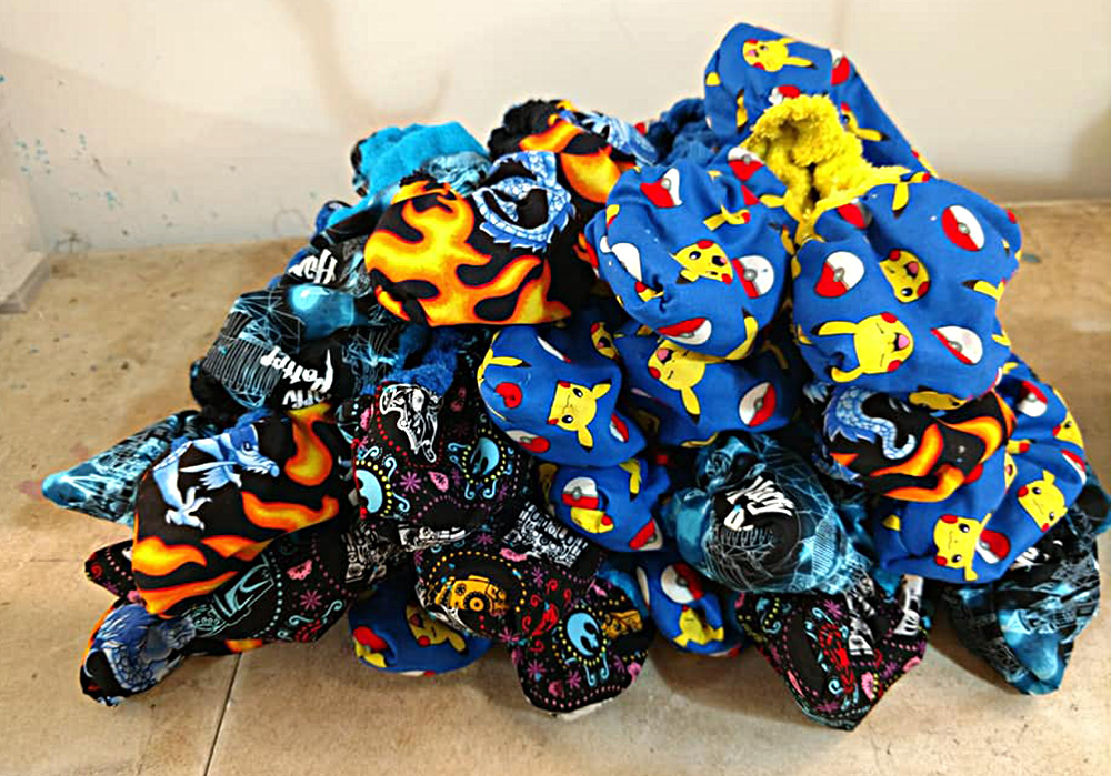 A pile of soakers in different, brightly coloured print fabric is shown on a work table.