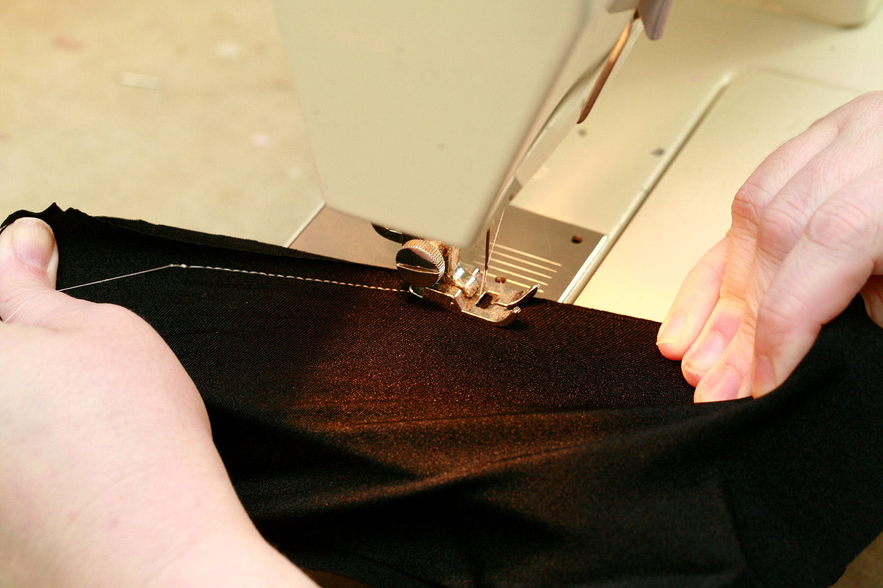 Two hands are sewing a piece of black spandex fabric with a stretch stitch, in a sewing machine.