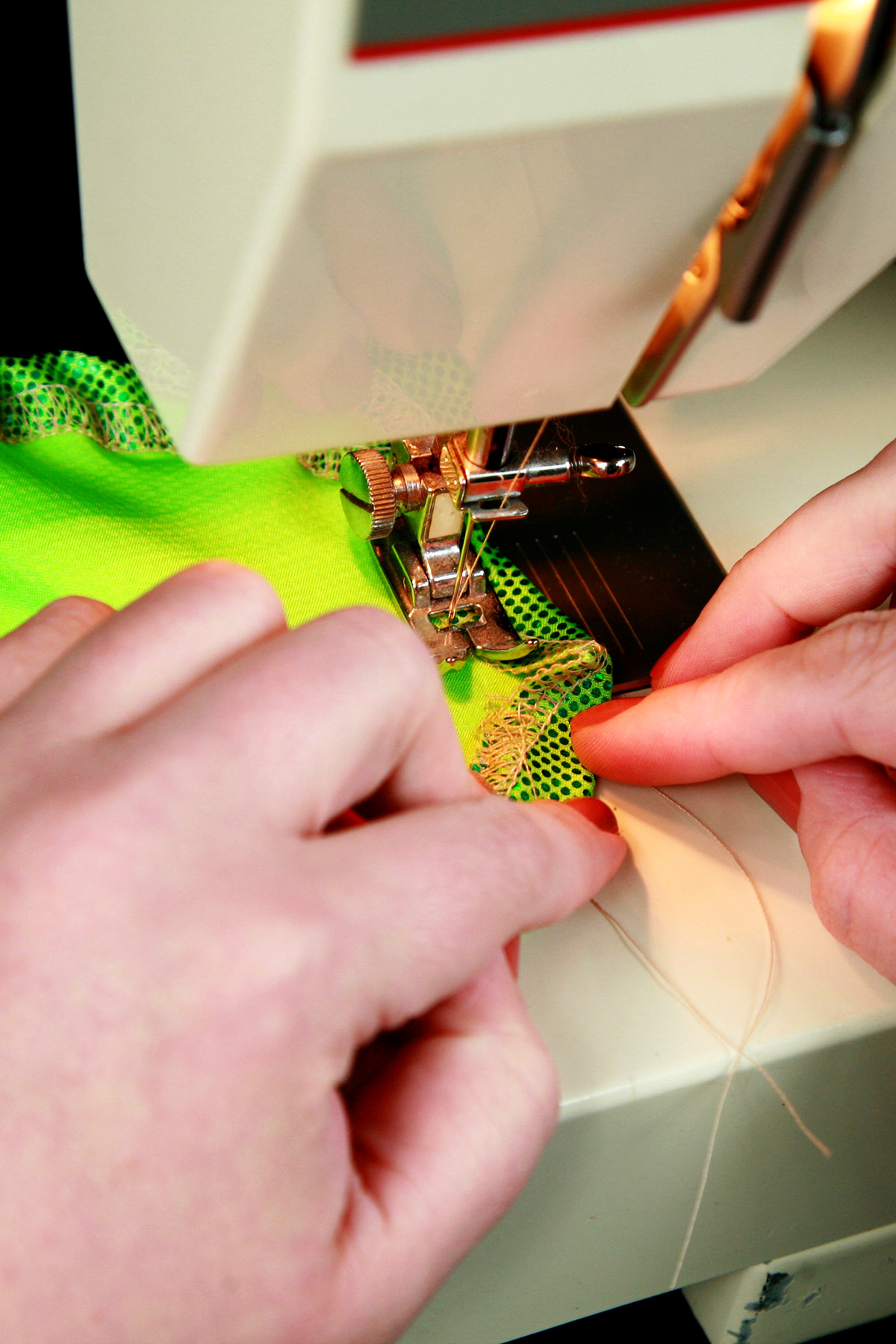 A pair of hands is sewing a bright green circle of fabric.