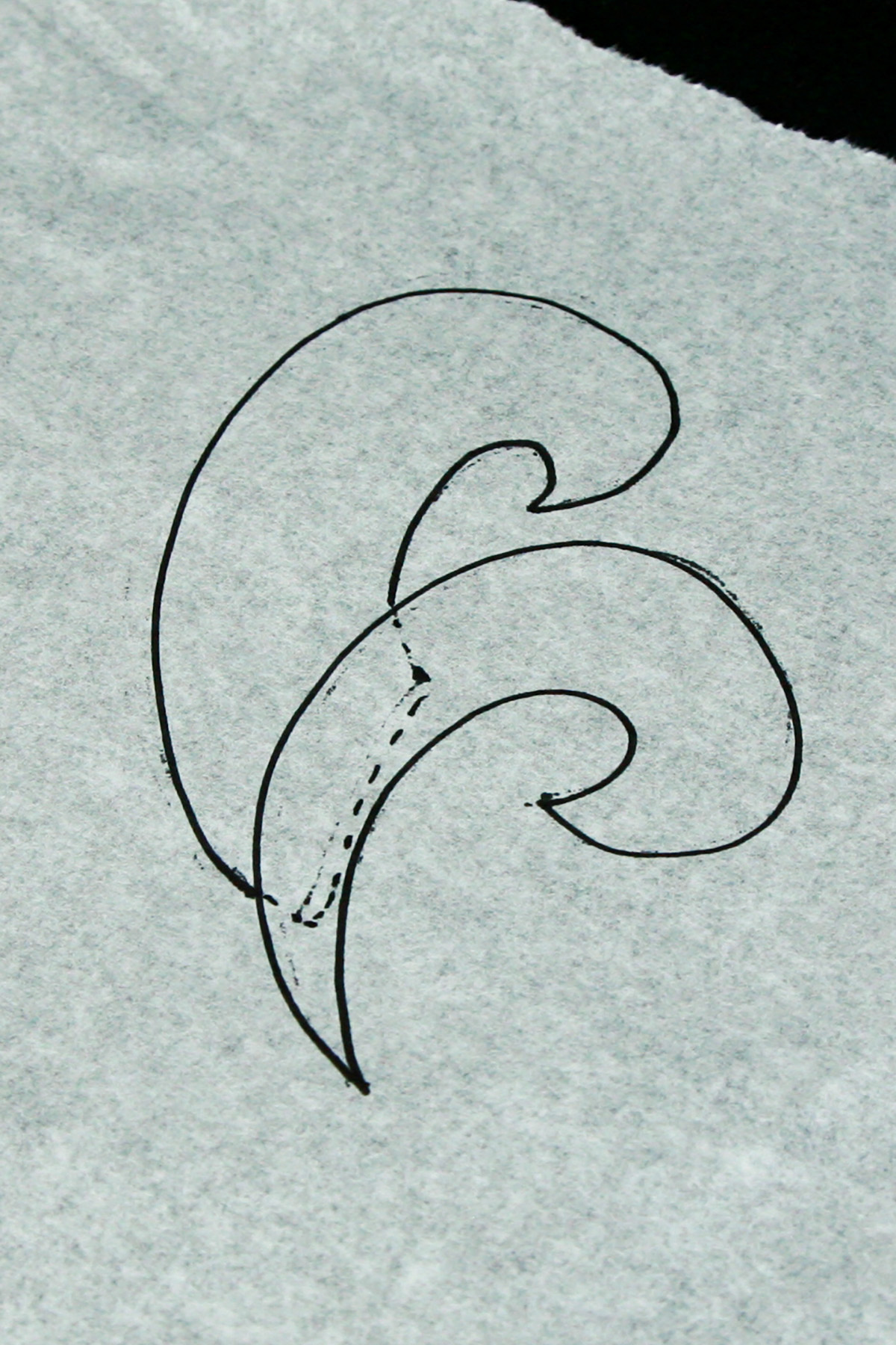 A small piece of paper with 2 swirls shapes drawn on it,in black marker.