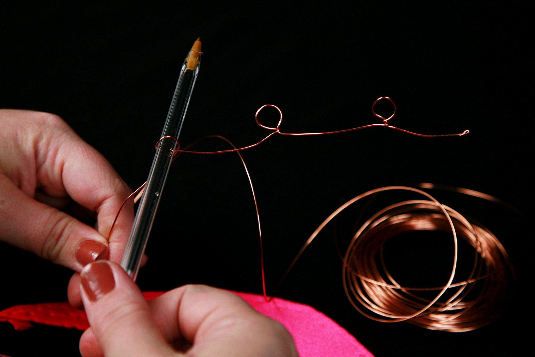 Two hands wrap a length of copper wire around a pen.