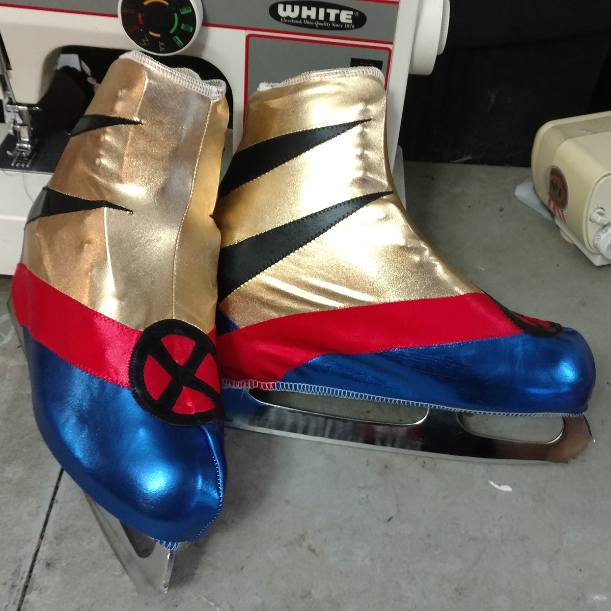 Gold, red, and royal blue skate covers with an X-Men logo and Wolverine slashes are shown on a pair of figure skates.