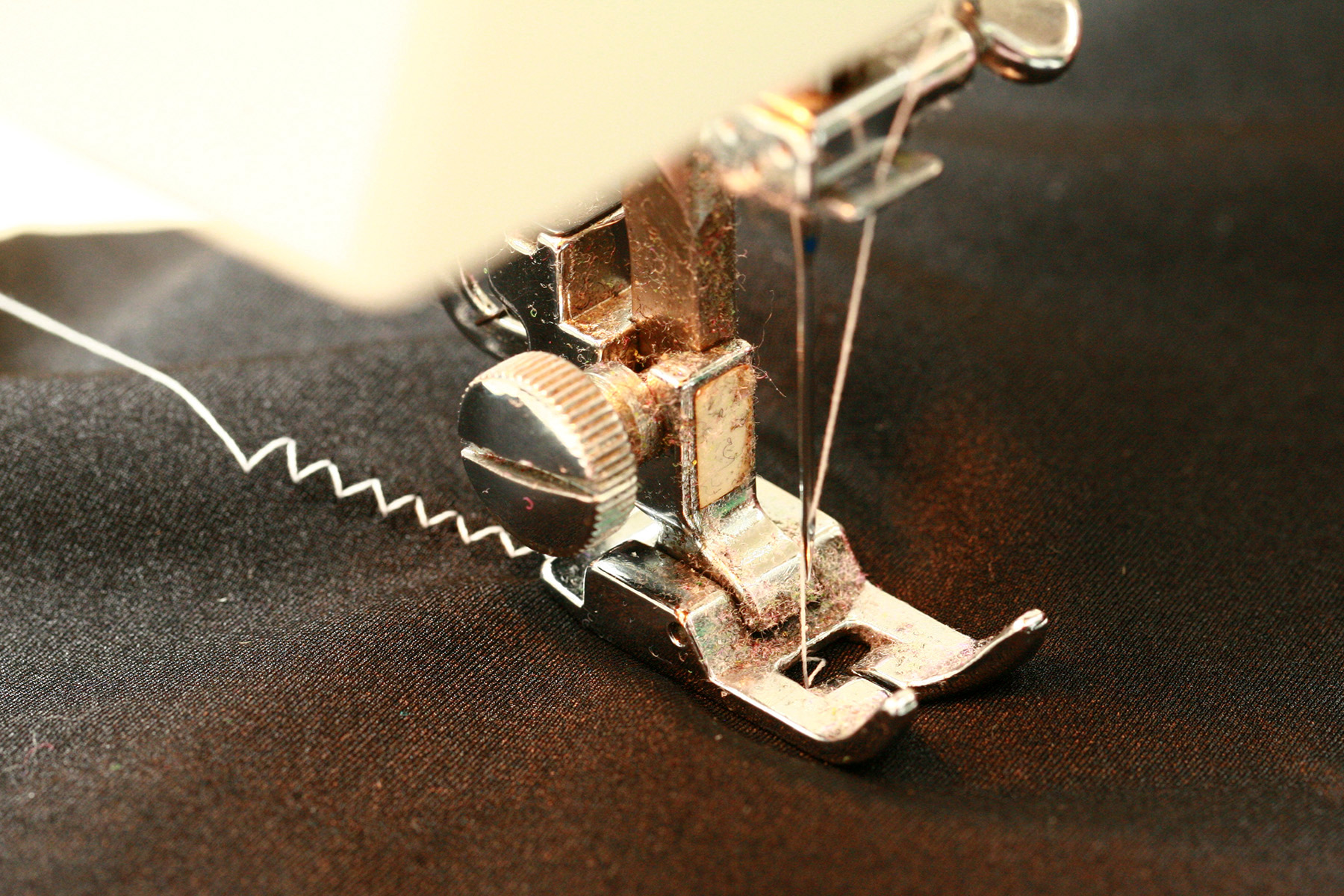 A close up view of a sewing machine sewing spandex with a zig zag stitch.