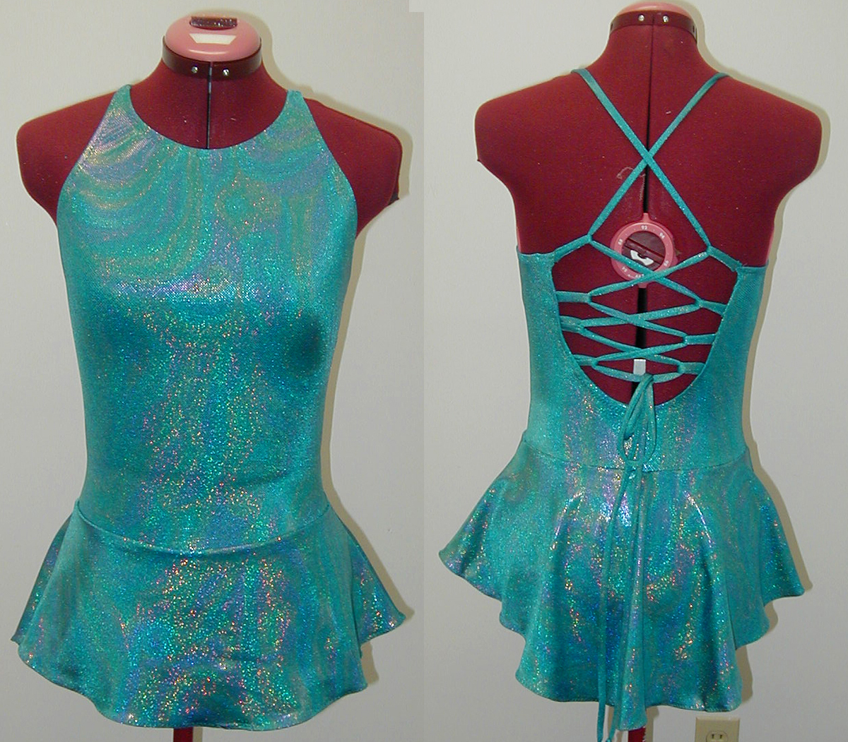 The front and back of a sleeveless blue skating dress. The back is wide open, with lacing criss-crossing it.