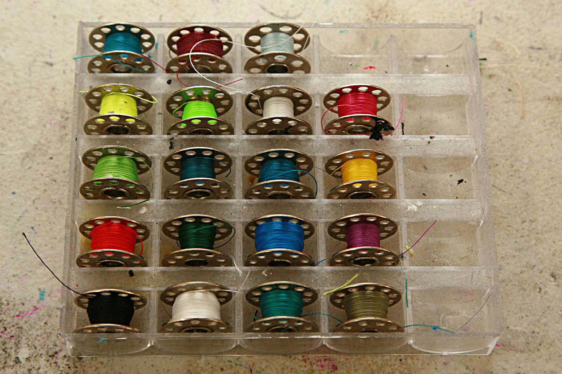 A plastic bobbin case, full of bobbins threaded with many different colours of thread.