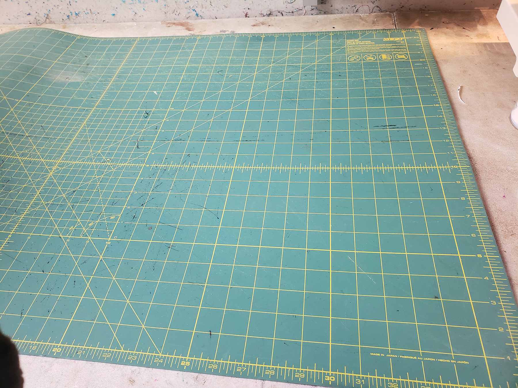 A large green cutting mat with yellow grid lines.