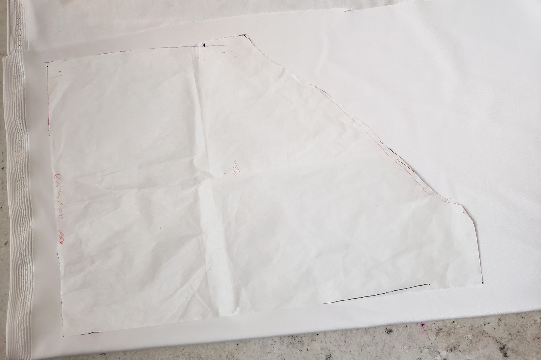 The back of a trunks pattern is resting on white spandex. The fabric is folded over, but the pattern is not lined up on the fold.