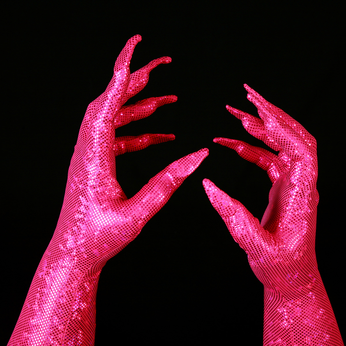 Two hands are shown wearing sparkly hot pink gloves, with built in claws.