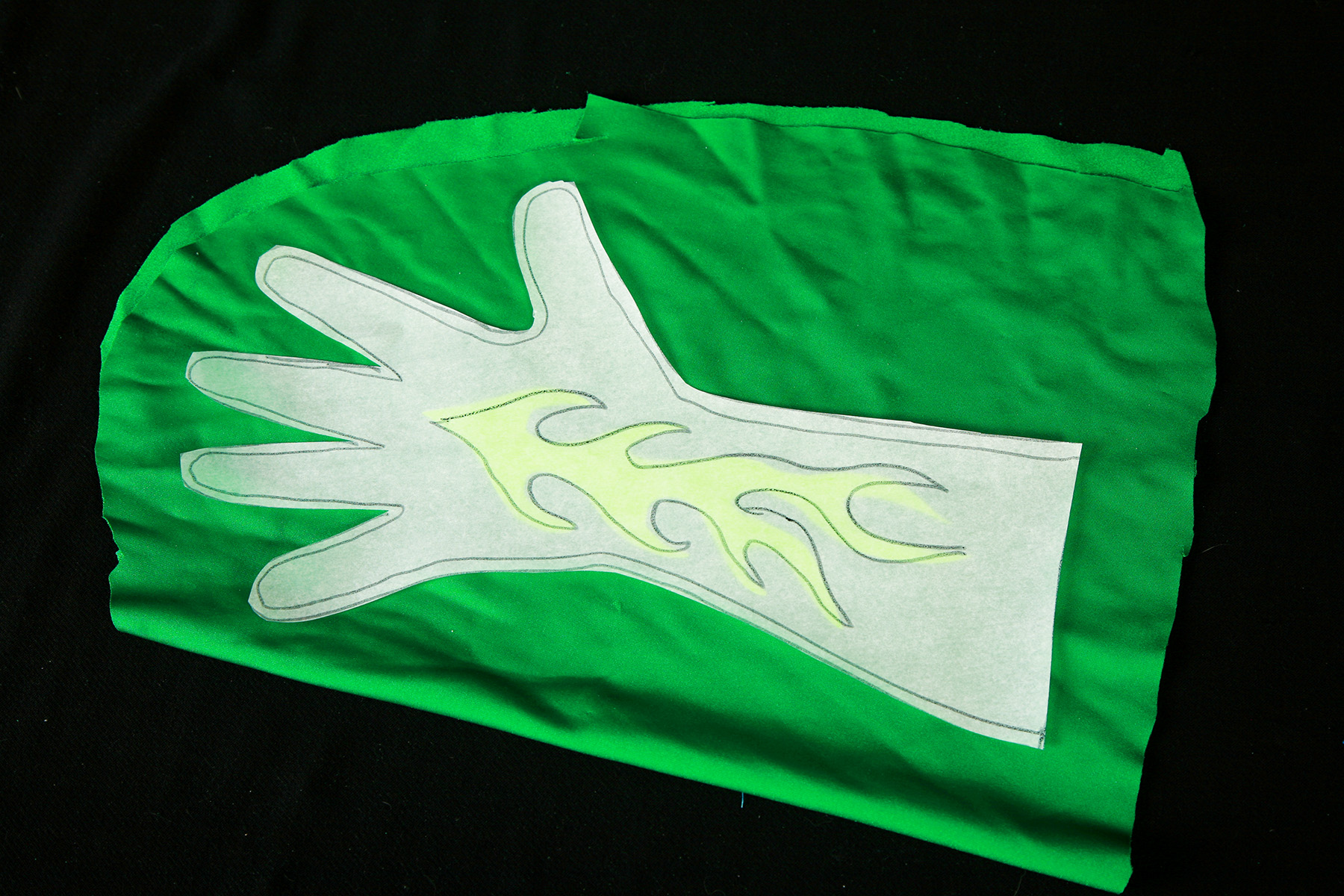 The glove pattern and flame are resting on top of a piece of dark green spandex.