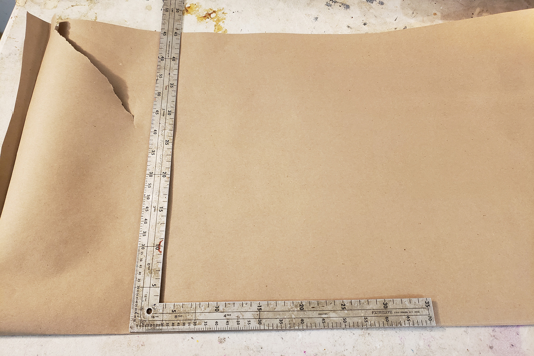 A metal square ruler rests on a large piece of brown craft paper.