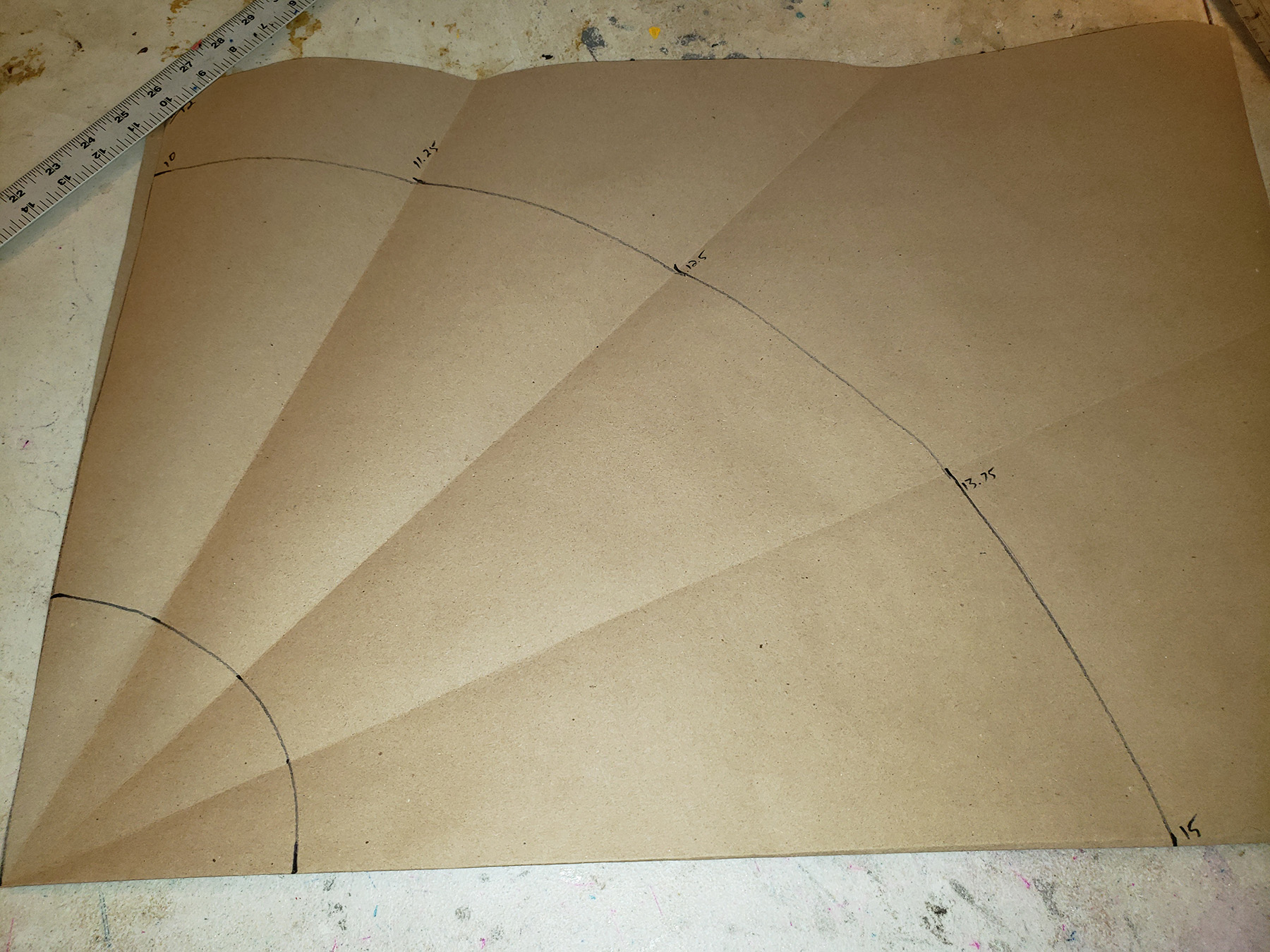 A circle skirt pattern drafted onto a folded piece of brown craft paper.