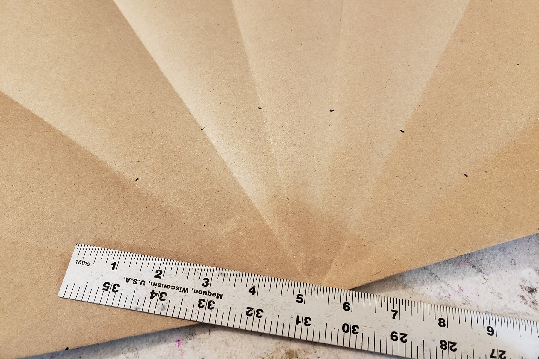 A large piece of brown craft paper with multiple folds radiating out from a central point.