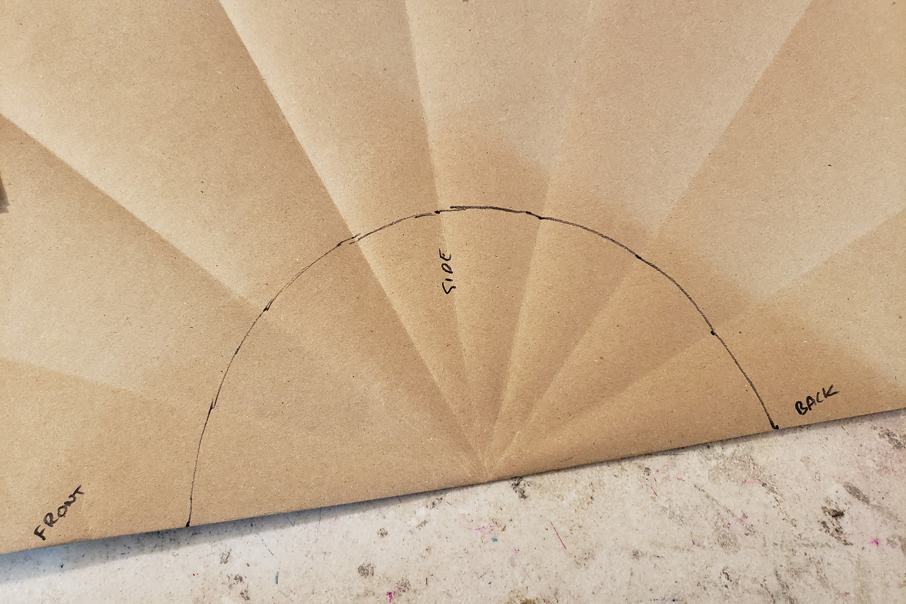 A large piece of brown craft paper with multiple folds radiating out from a central point.  A semi circle is drawn around the join point of the folds.