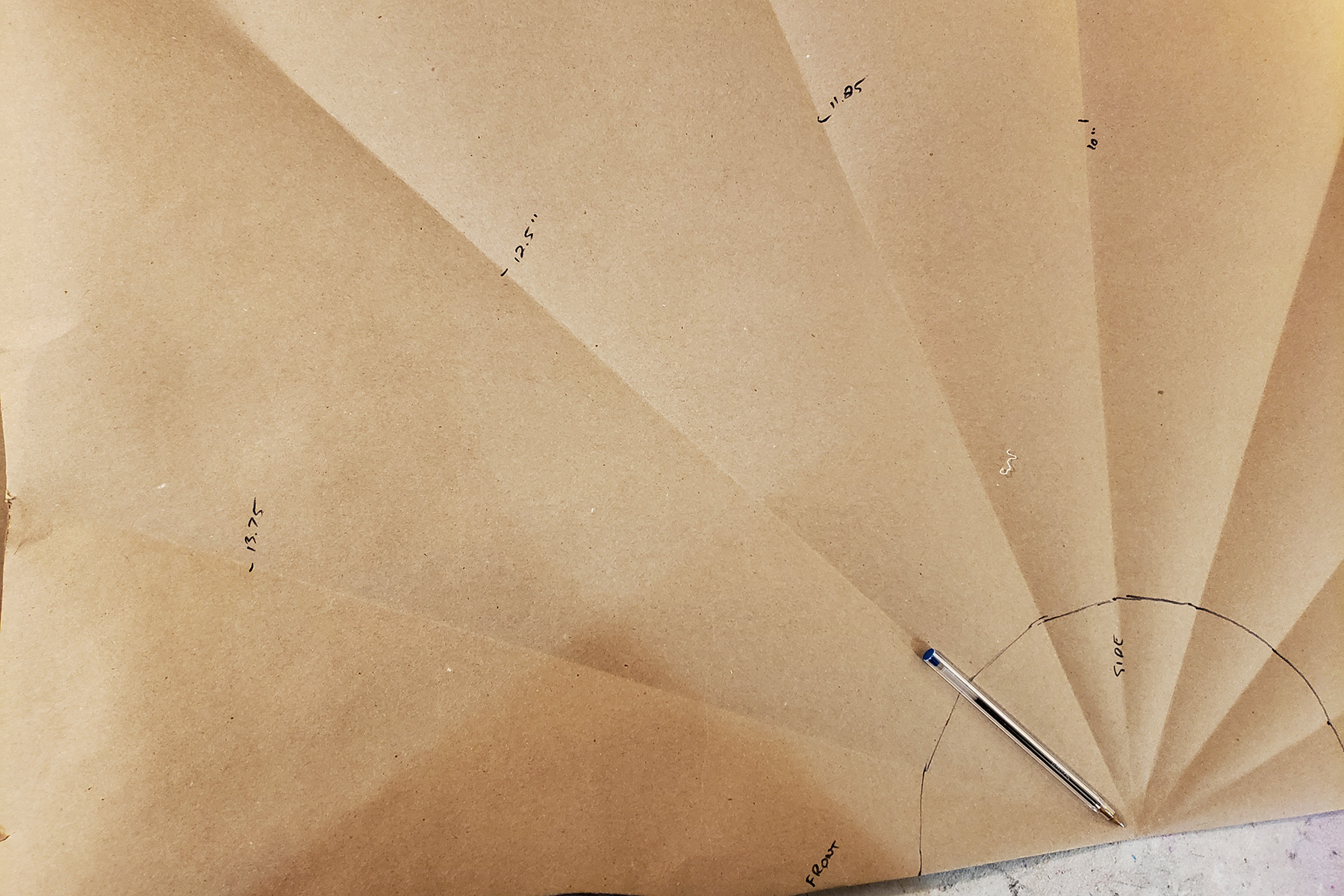 A circle skirt is being drawn over all of the marked points on a piece of brown craft paper.