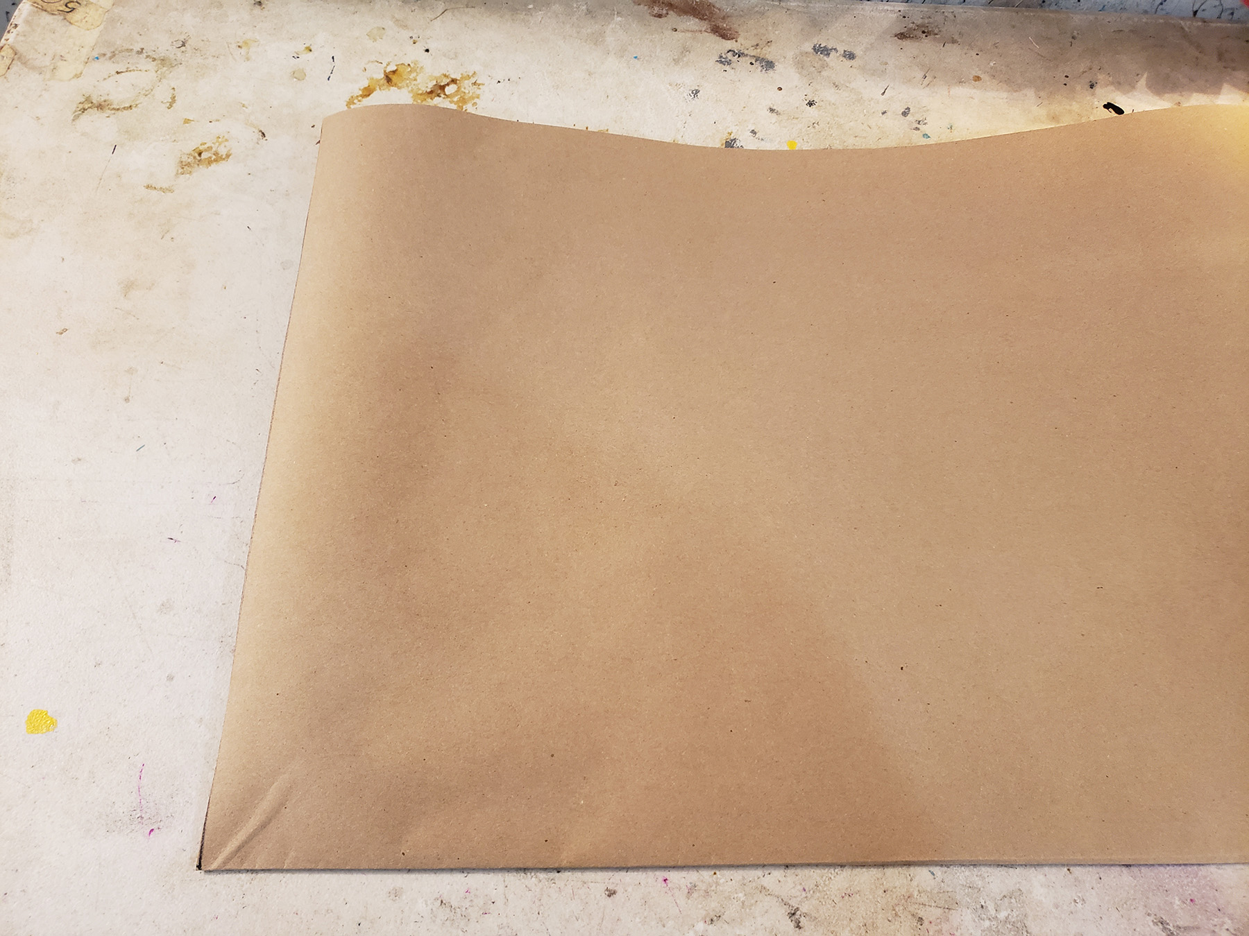 A large piece of brown craft paper on a work table.