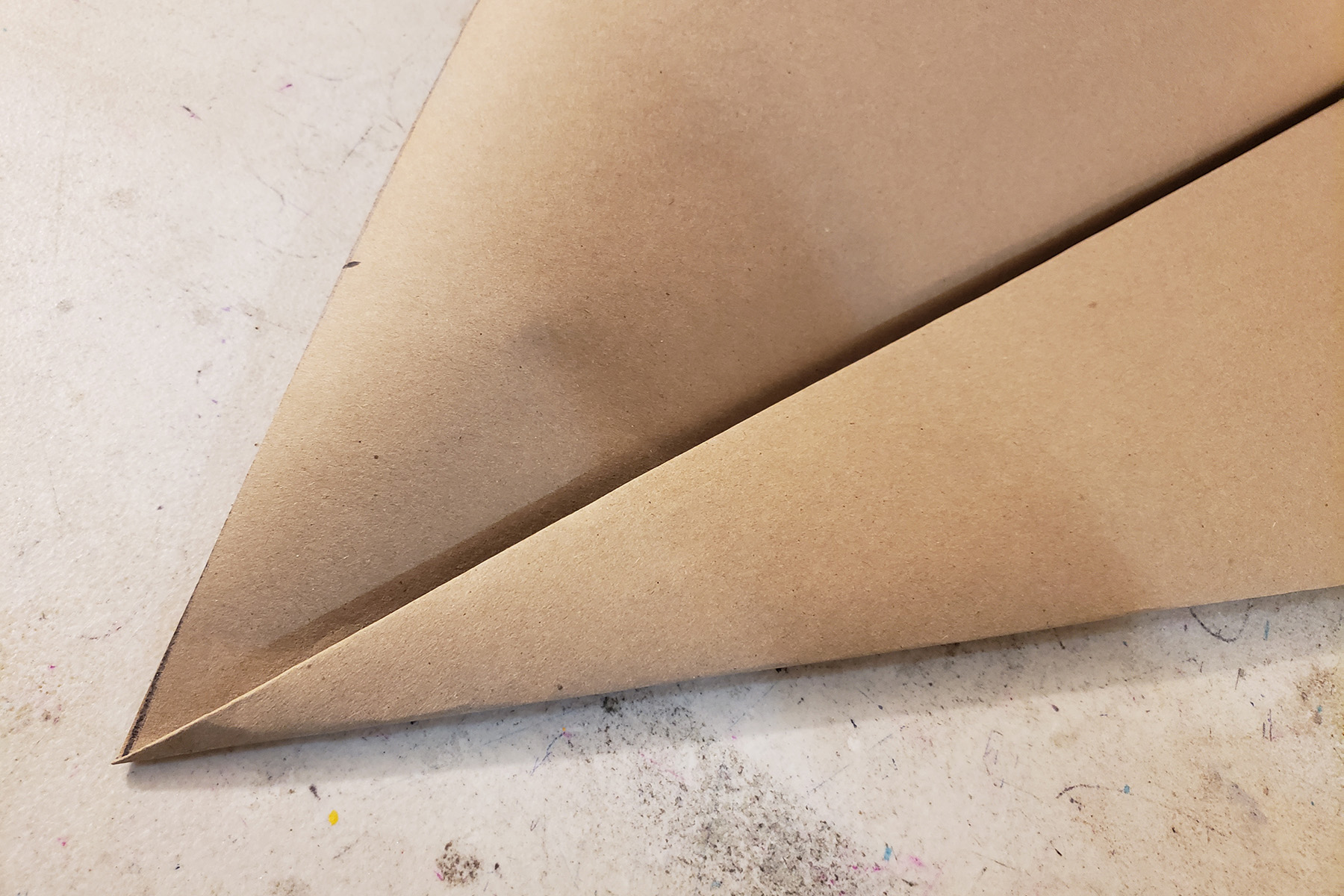 A piece of brown craft paper has been folded several times.