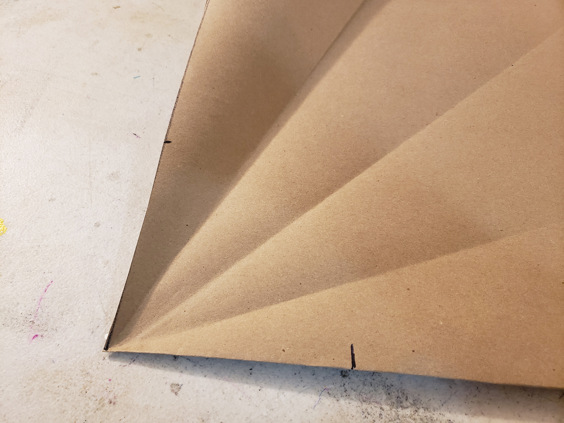 A piece of brown craft paper with fold marks radiating out from one corner.