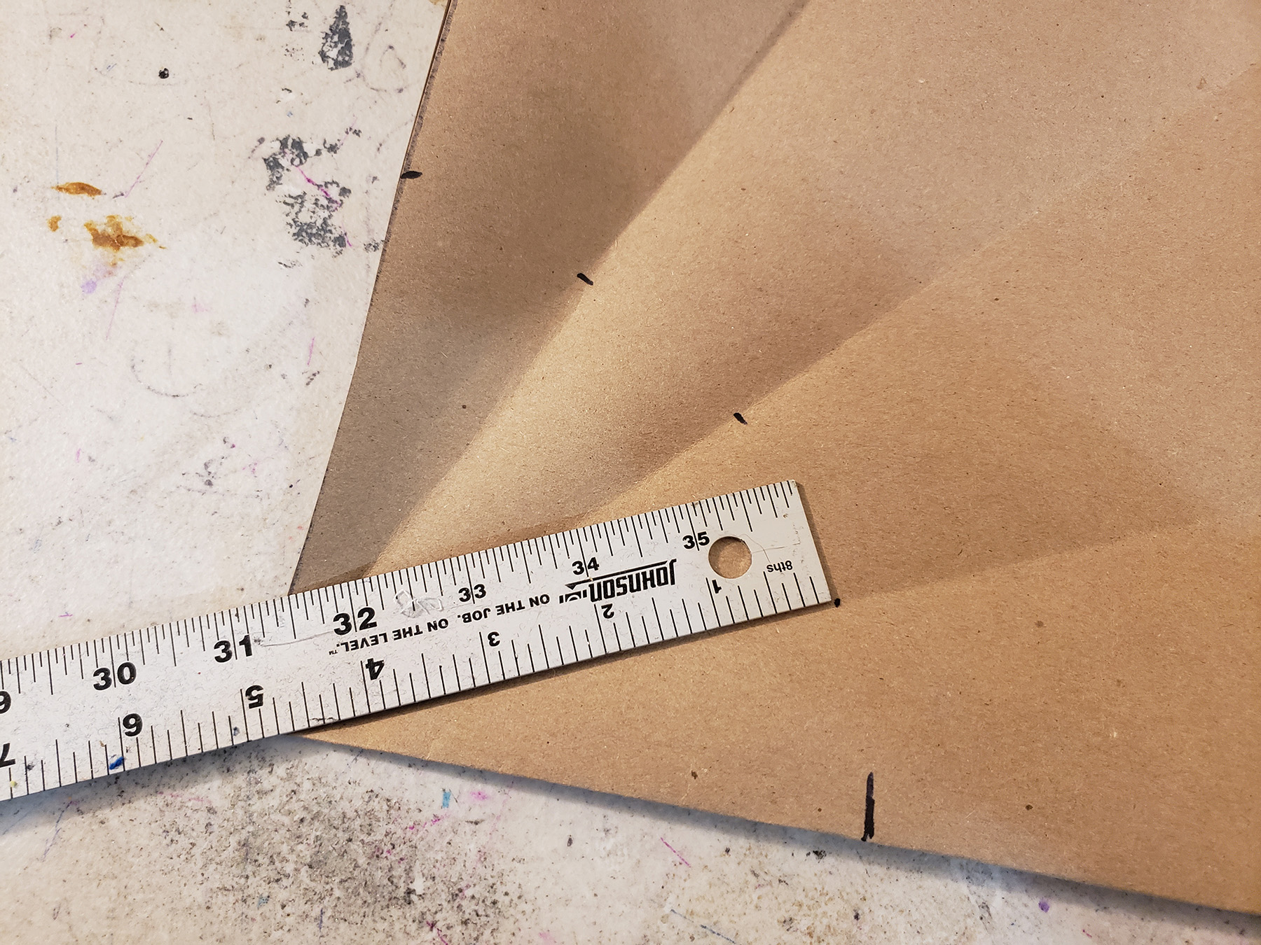 A metal ruler is shown on a piece of brown craft paper, with several black marks along fold lines.