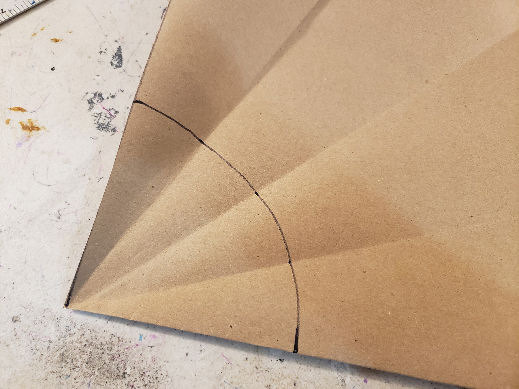An unfolded piece of brown craft paper has a curve drawn from one side to a side perpendicular to it.