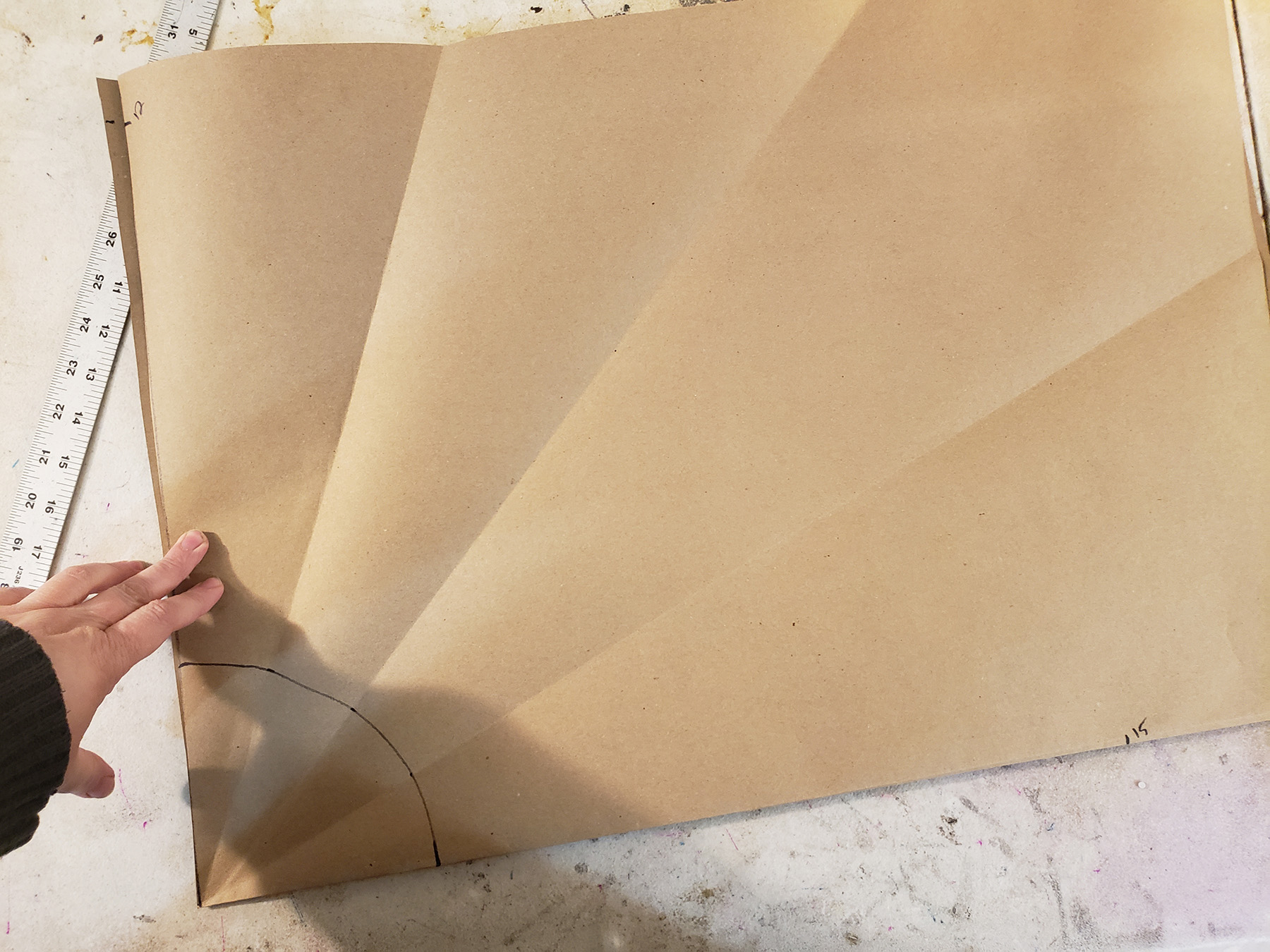 A large piece of brown craft paper has several fold lines radiating out from a corner, and a black semi circle drawn at that corner.