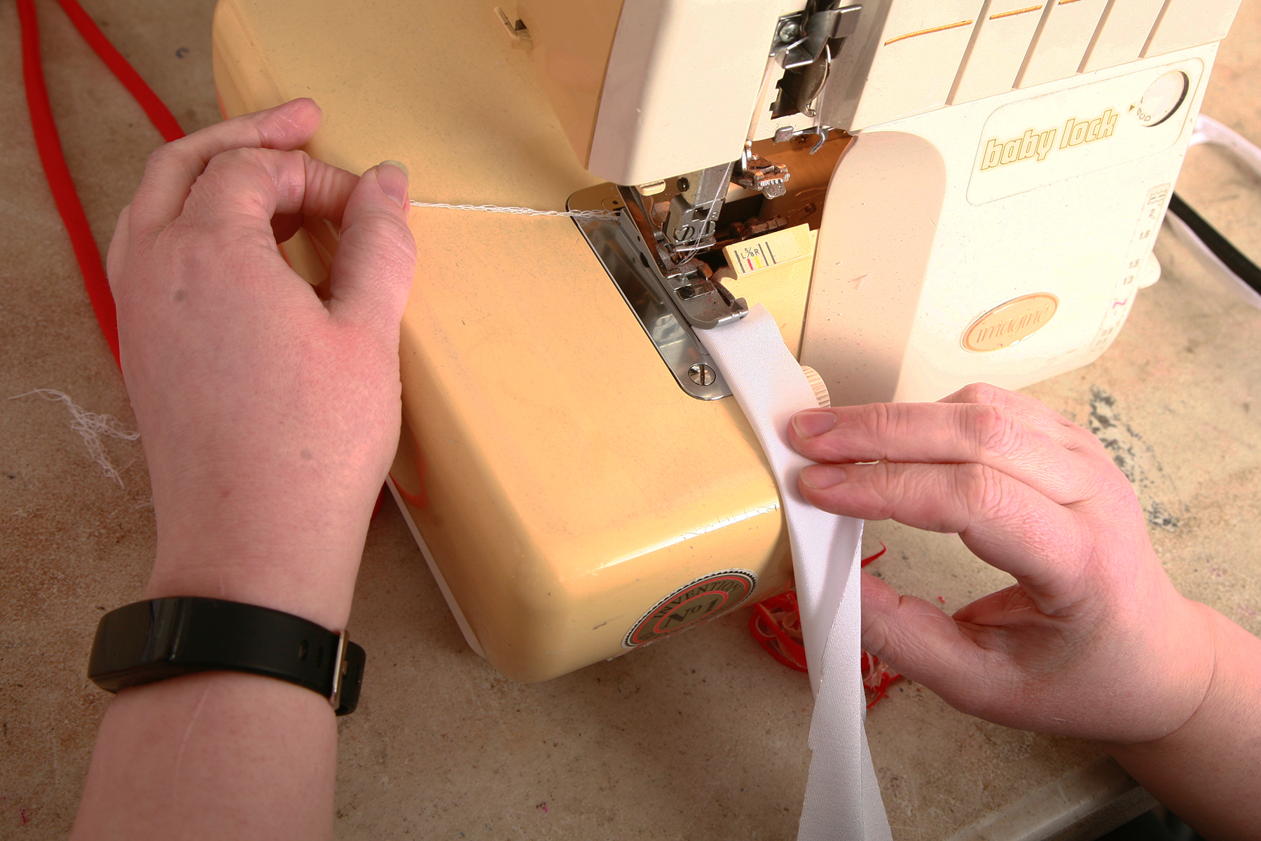 Two hands are feeding a piece of white fabric through a serger.