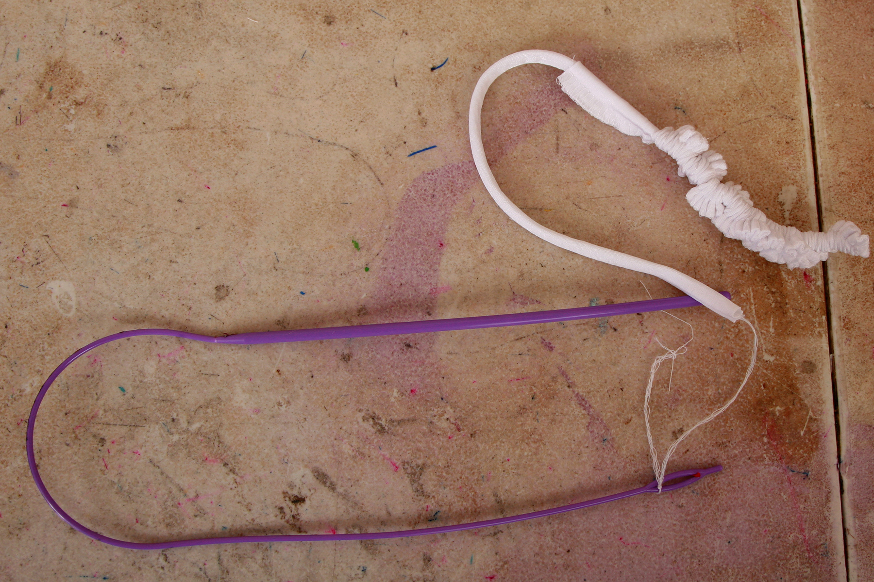 A long white bikini string is being pulled off the end of a purple cord threader.
