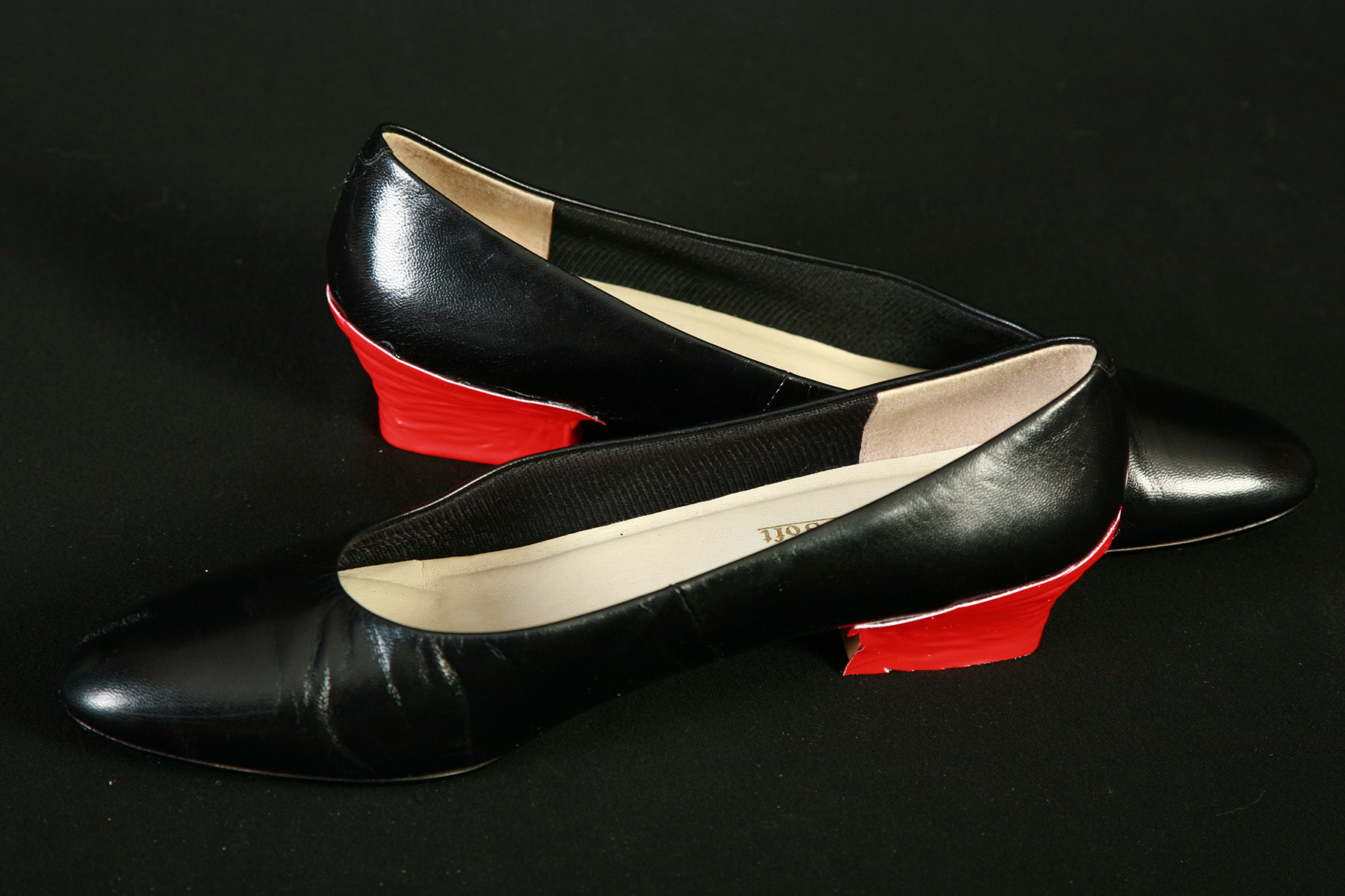 Two black shoes with red fabric covering the heels.
