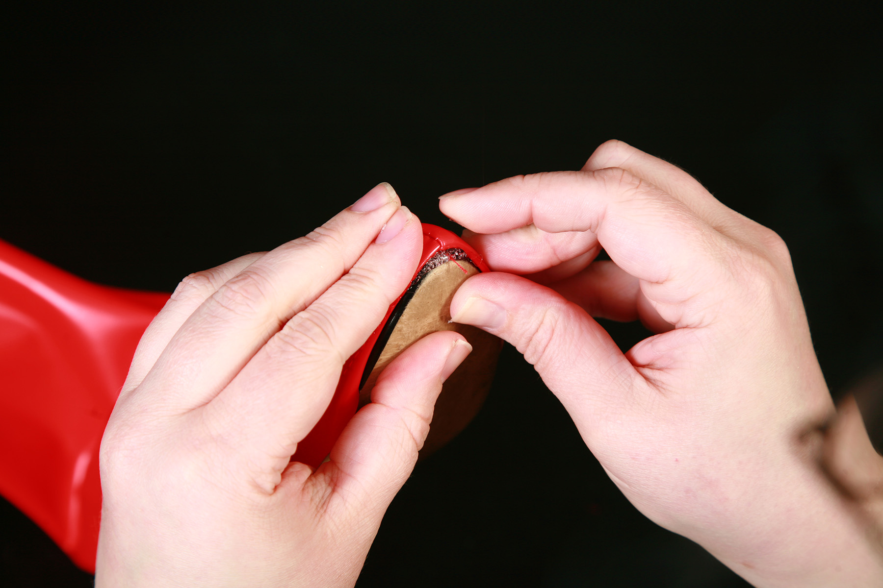 Two hands are pressing red spandex down around the toe of a shoe.