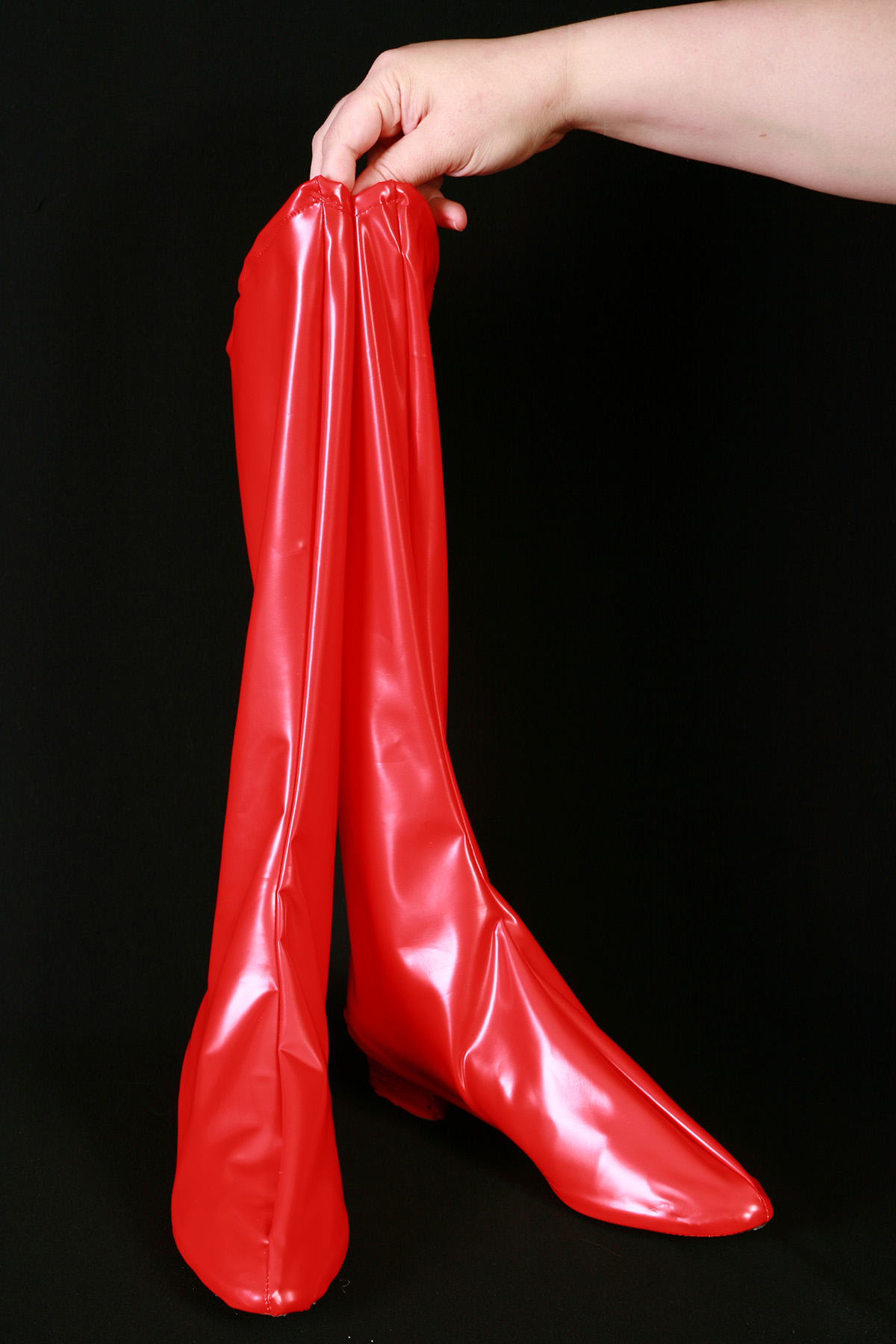 A hand holds up a shiny pair of bright red spandex boot covers.