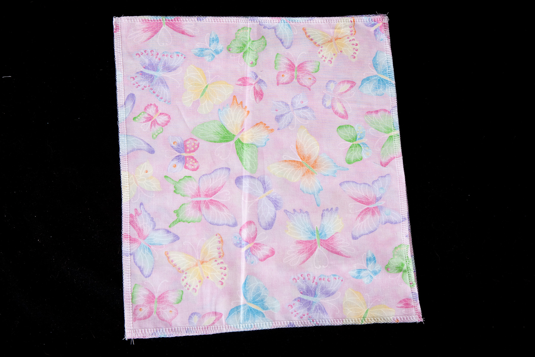 A rectangle of light purple butterfly print fabric against a black background.