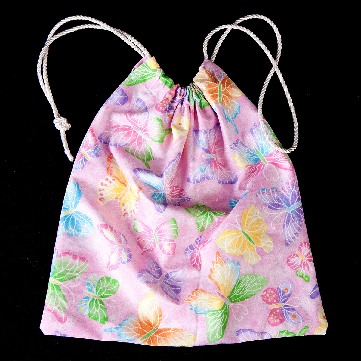 A light purple butterfly print Grip Bag, with a white drawstring cord. It is against a black background.