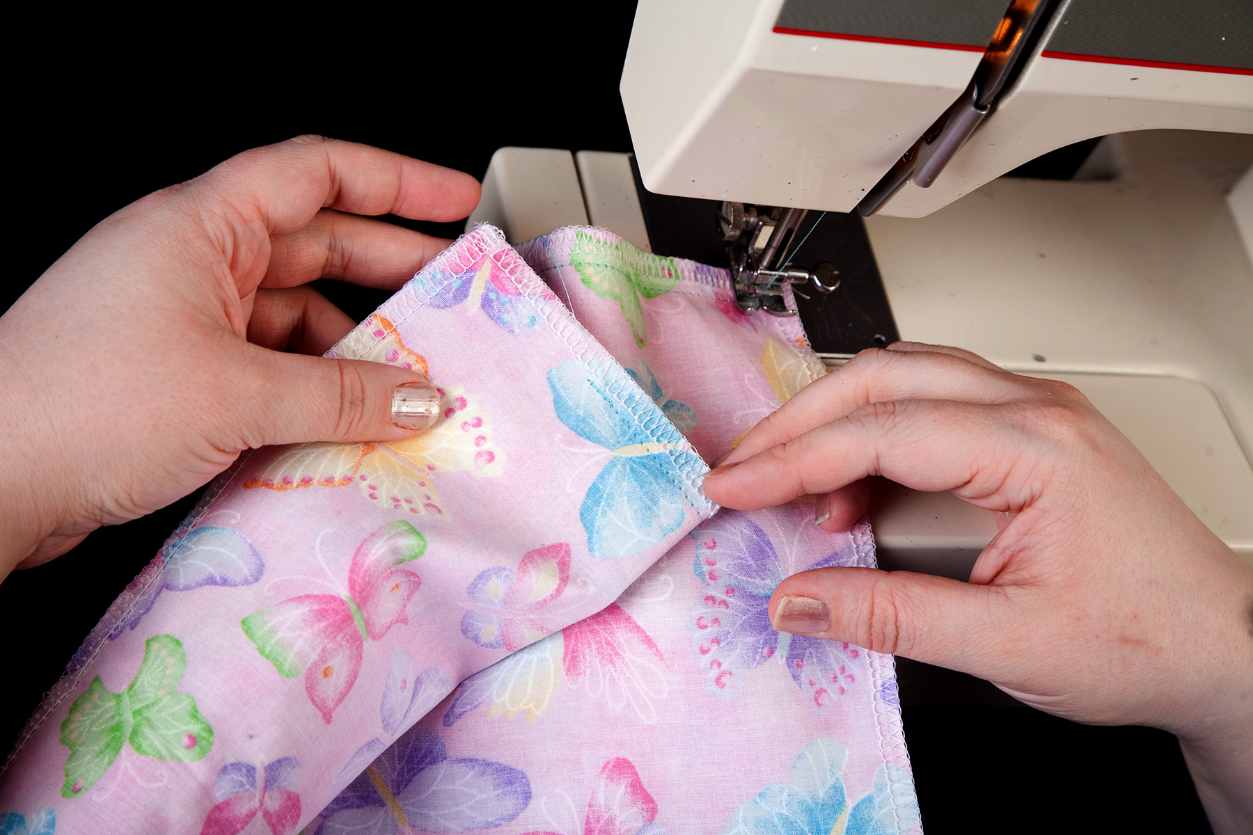 A pair of hands shows a seam on light purple butterfly print fabric.