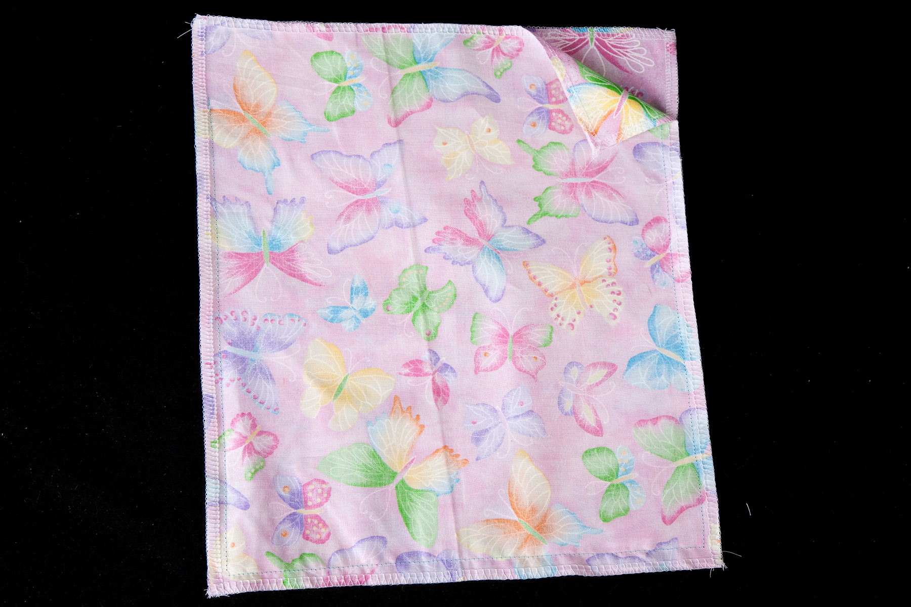 Two rectangles of light purple butterfly print fabric - sewn together. One corner of the upper layer is flipped back to show the inside.
