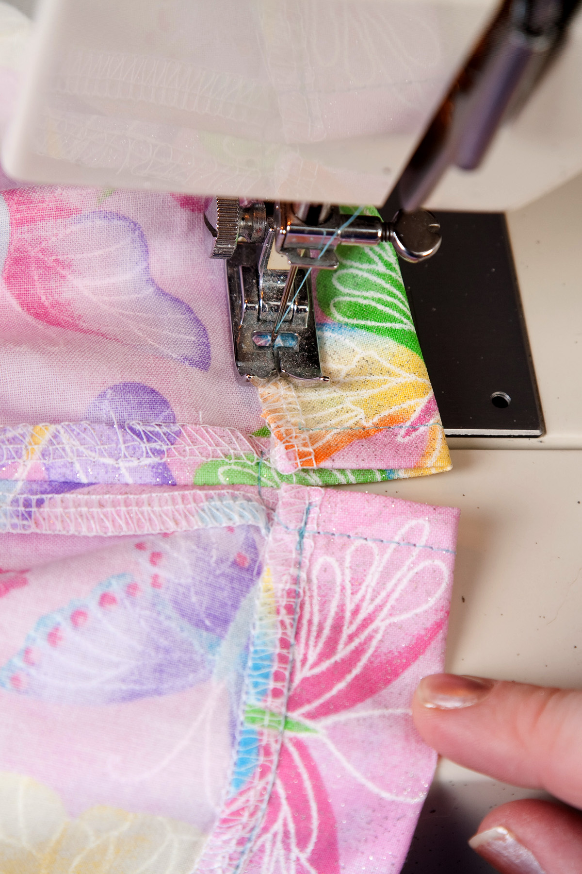 """A 1"""" seam is turned over and being sewn down by a sewing machine."""