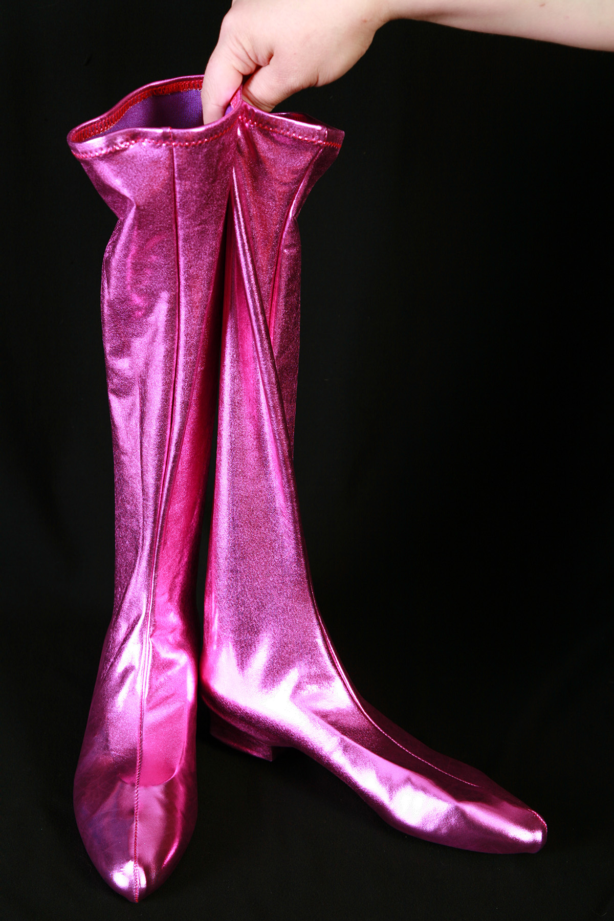 A pair of shiny purple spandex boot covers on a black background.