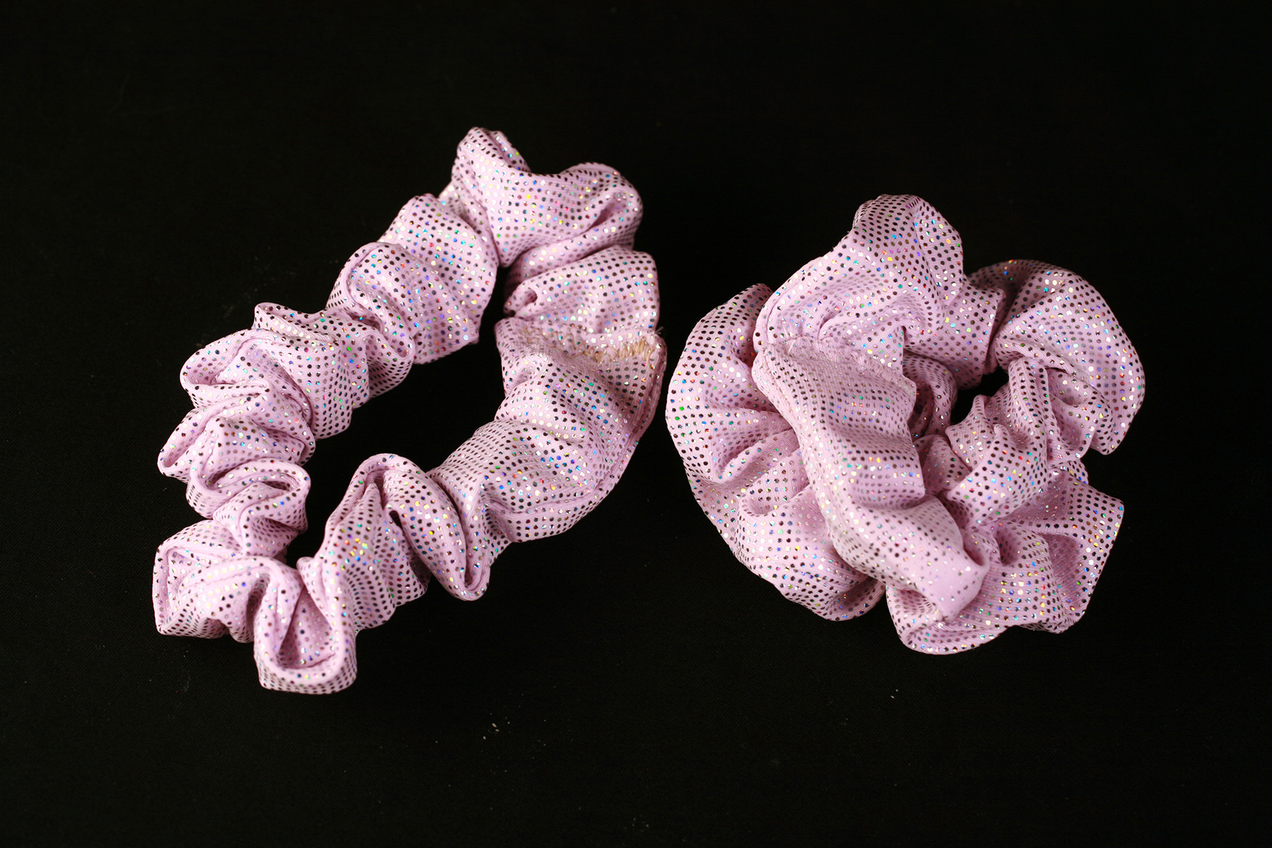 Two sparkling light pink scrunchies are shown against a black background.