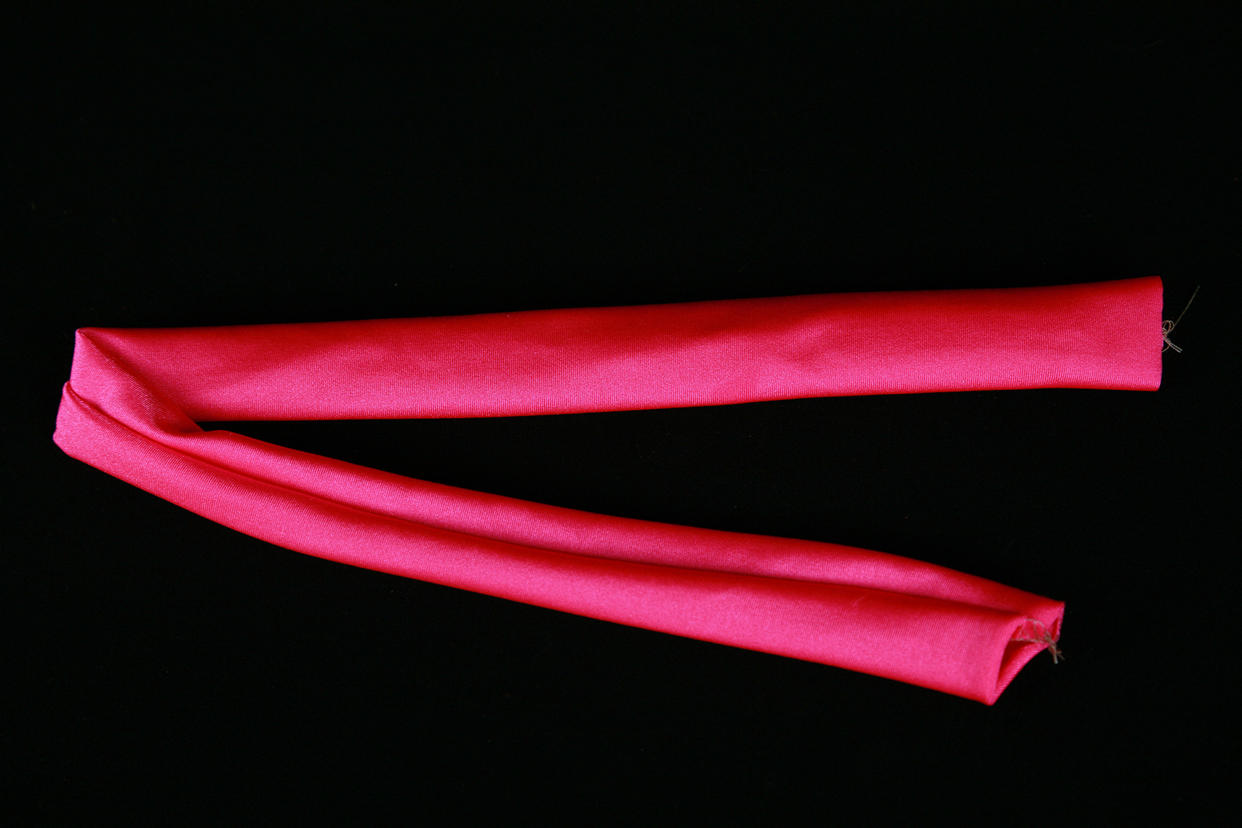 A tube of hot pink spandex is shown against a black background.
