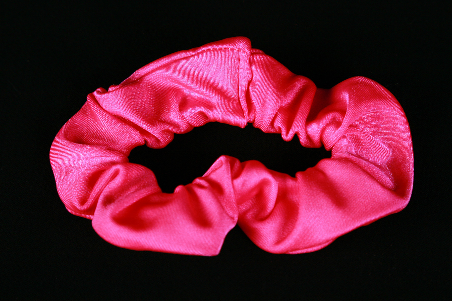 A close up image of a hot pink spandex scrunchie.