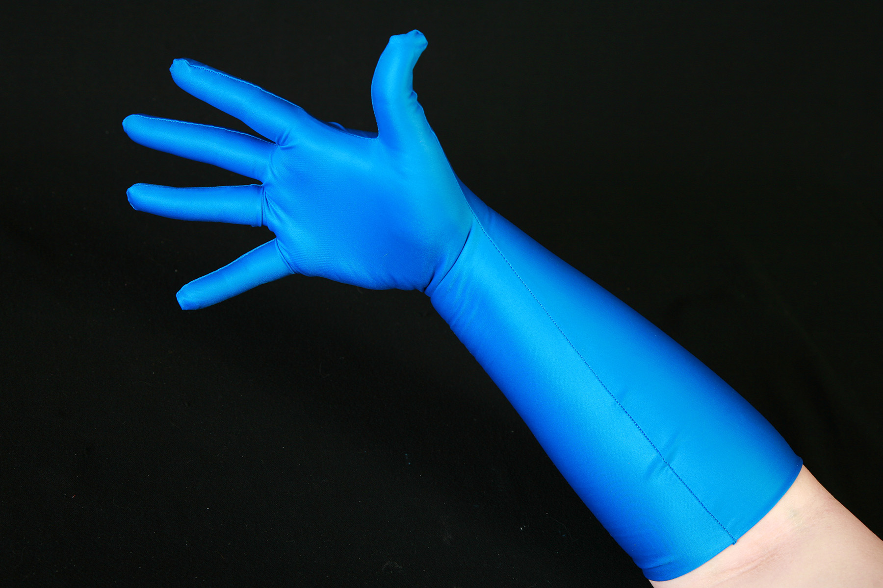 A hand wearing a blue spandex glove against a black background.